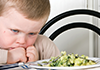 Toddler boy looking at plate of food